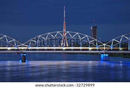 The night express train on the bridge across Daugava river. - stock photo