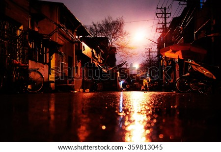 The night light reflection on a wet asphalt in Shanghai slums - stock photo
