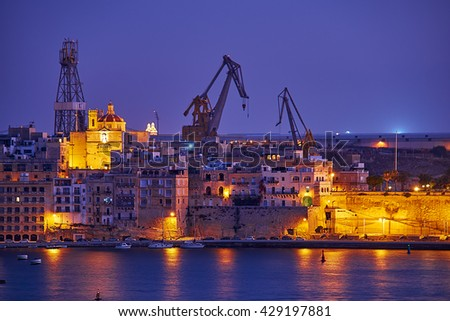 The night view of Senglea with the port cranes on the background from the Lower Barrakka Gardens, Valletta, Malta