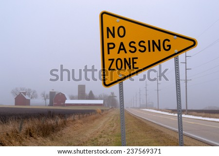 """The """"No Passing Zone"""" sign on the rural country road on a foggy day. - stock photo"""