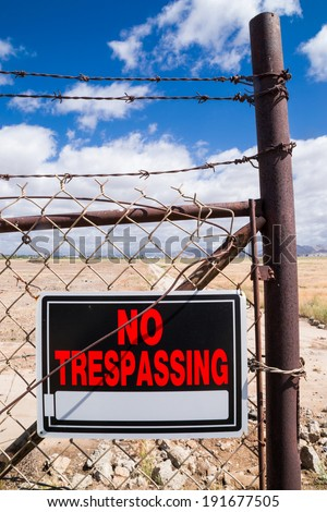 "The ""No Trespassing"" sign on the rusty chain link fence. - stock photo"