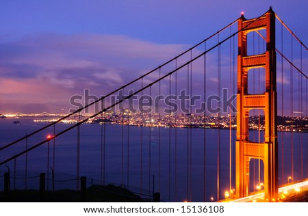 The North Tower of Golden Gate Bridge against the background of Bay Bridge and San Francisco skyline, shot from Battery Spencer (Marin Headlands) at dusk. - stock photo