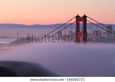 The north tower of the Golden Gate Bridge draped in morning fog with beautiful San Francisco in the background.  - stock photo