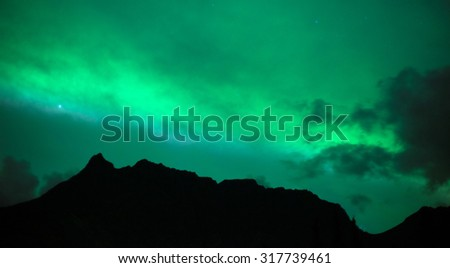 The Northern Lights emerge through the clouds in remote Alaska - stock photo