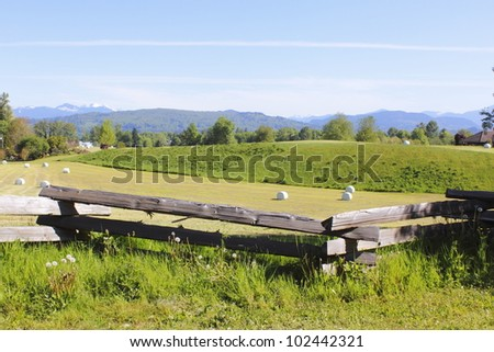 The Northshore Mountains overlooks farmland in British Columbia's Fraser Valley/Scenic Farmland/Farmland in British Columbia's Fraser Valley - stock photo