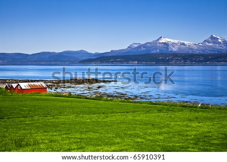 The Norwegian fishing small houses on the bank of lake - stock photo