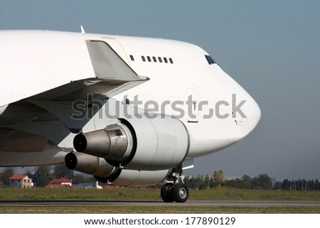 The nose of a large white taxiing plane at the airport - stock photo