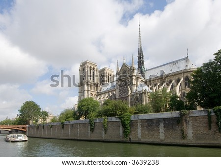 The Notre Dame in Paris, seen from the opposite side of the river Seine. A river boat takes the tourists past all the sites; the sun strikes the roof tops of the cathedral beautifully
