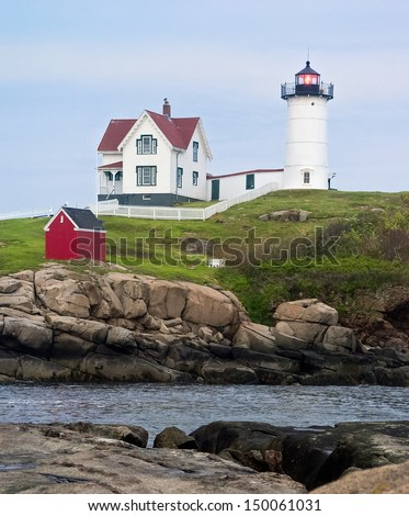 The Nubble Light is a lighthouse on a small rocky island at Cape Neddick near York, Maine. - stock photo