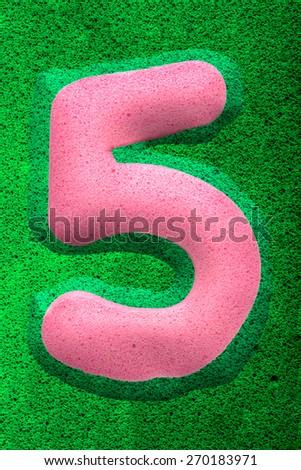 The number five in a pink sponge like texture, raised 3D from the green background.