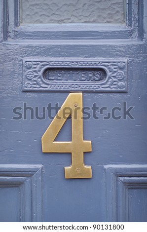 The number four in brass attached to a house front door - stock photo