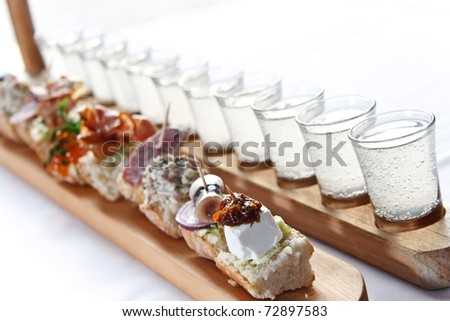 The number of shots and appetizers on wooden bars - stock photo