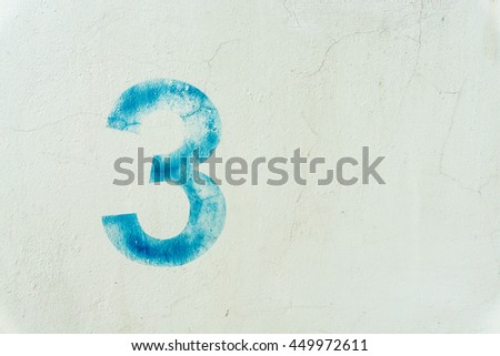 the number 3 on the dirty white wall