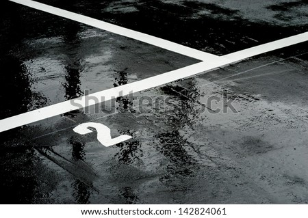"The number ""2"" printed on the wet road. - stock photo"
