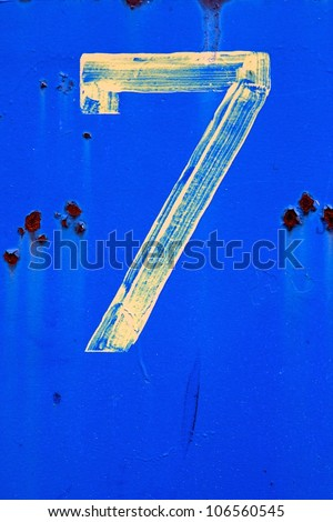 The number 7 (seven) painted in faint yellow on a vibrant blue background at an industrial facility. - stock photo