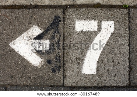 The number seven painted on the footpath pointing to the nearest parking meter - stock photo