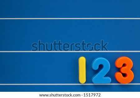 The numbers 1, 2 and 3 from a child's toy alphabet set, placed on a blue, lined background. Space for text elsewhere in the image.