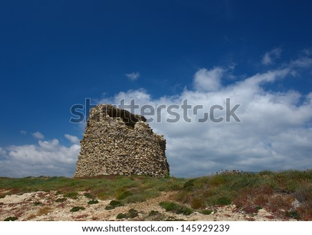 The nuraghe (nuraghi, nuraghes) is ancient megalithic edifice,symbol of Sardinia and the Nuragic civilization.Ancient traditional nuraghe building in Sardinia,Italy on sunny and cloudy sky background