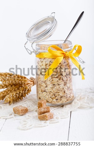 The oat flakes in glass jar with brown sugar.