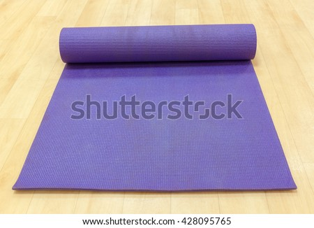The object sport equipment background purple yoga mat on wood background in exercise room or gym and fitness room. - stock photo