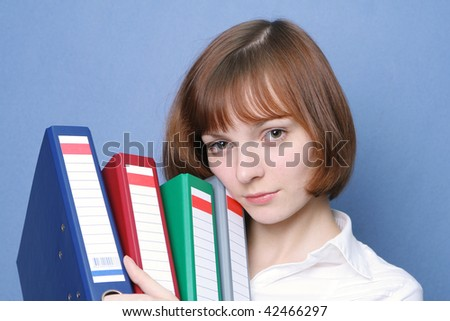 The occupied business woman with multi-colored folders. The head lies on folders - stock photo