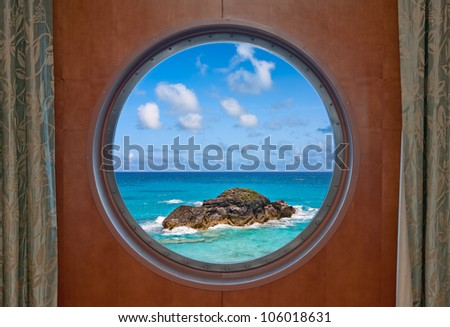 The ocean and a large boulder seen through the porthole of a cruise ship - stock photo