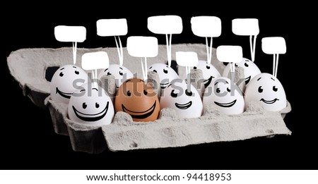 The odd one, funny eggs with smiley faces - stock photo