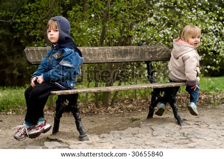 The offended boy and the girl sit on a bench in park - stock photo