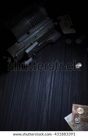 The old adding machine on the dark blue wooden table with money around.