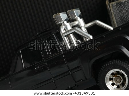 The old and dirty black color radio control model toy pick up car among the dark background scene. - stock photo