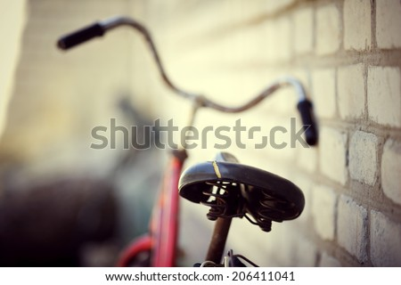 the old bicycle costs at a house wall - stock photo