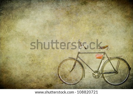 The old bicycle on the old brown paper - stock photo