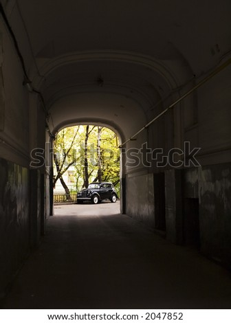 The old black car stopped opposite to an arch