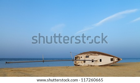 The old boat lying on the beach. - stock photo