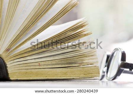 The old book and glasses  in close up view.Shallow DOF - stock photo