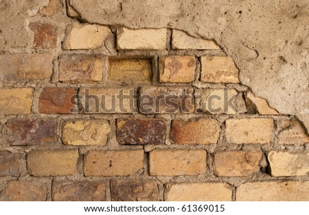 The old brick wall with crumbling plaster