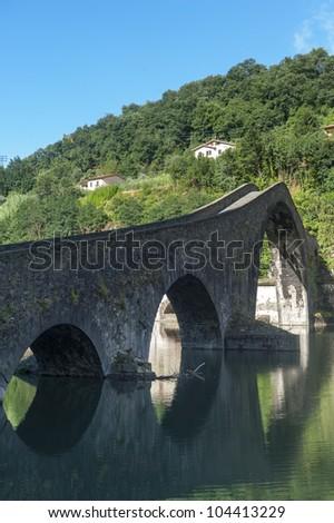 The old bridge known as Ponte della Maddalena, near Borgo a Mozzano (Lucca, Tuscany, Italy), on the Serchio river - stock photo
