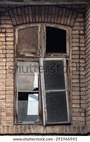 The old broken wooden windows on abandoned house. - stock photo