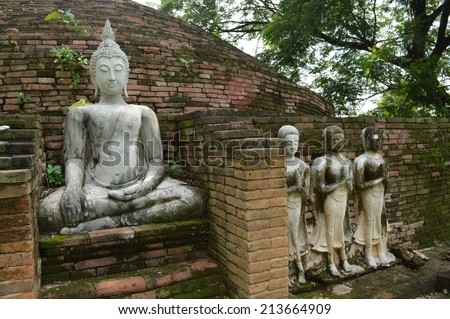 The old Buddha image and his followers in the ancient temple in Northern of Thailand with gorgeous nature that provided by nature. - stock photo