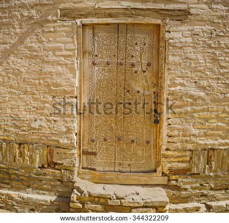 The old carved wooden door leads to the old house in Itchan Kala, Khiva, Uzbekistan.