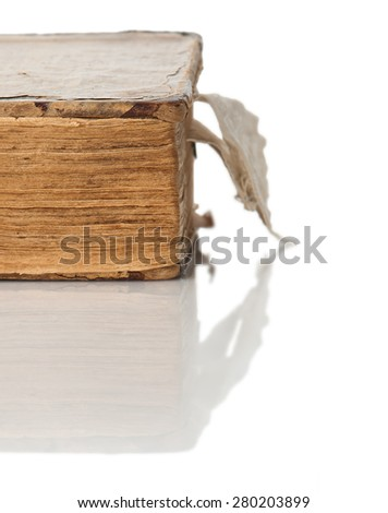 The old closed book with the turned yellow pages close up on a white background with reflection. - stock photo