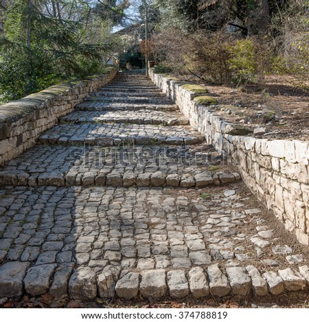 The old cobbled pavement stone steps leading to the residential buildings area - stock photo
