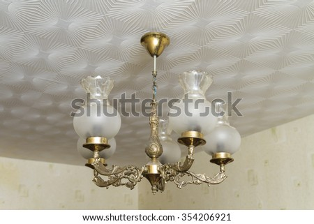 The old copper chandelier hanging from the ceiling. - stock photo
