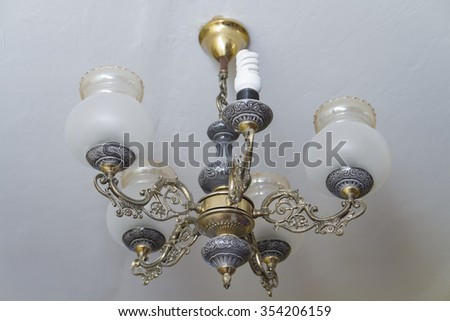 The old copper chandelier hanging from the ceiling with economical lamp. - stock photo