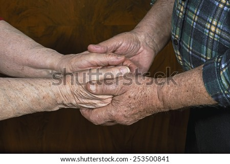 The old couple holding hands - stock photo