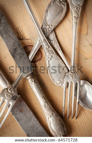 the old cutlery on wooden table - stock photo