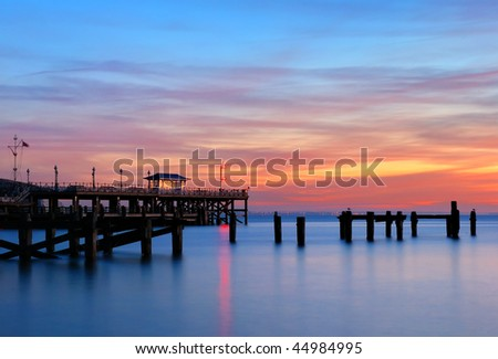 The old, derelict pier and the replacement Victorian pier in Swanage, Dorset. - stock photo