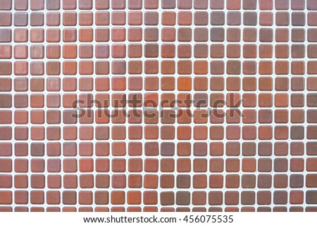 the old, dirty, alkali, rust dark brown and red chipped wall tiles of the building background texture