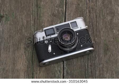the old film camera lies on a wooden table - stock photo