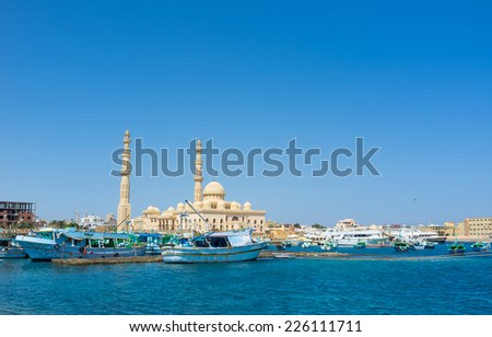 The old fishing boats in port next to the fishing market and Central Mosque on the background, Hurghada, Egypt. - stock photo